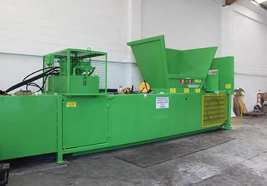 large green compactor next to a pile of cardboard boxes