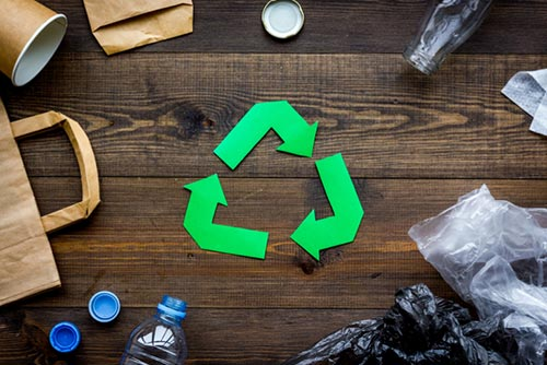 bottles bags and other recyclable material are placed on a wooden desk surrounding 3 green arrows that resemble the recycling logo