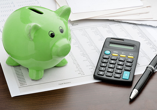 green piggy bank on a office desk next to a calculator and note pad