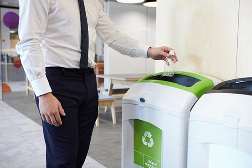 man in office attire putting a clear plastic bottle into a green recycling container