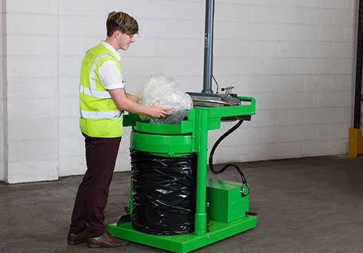 phs waste kit staff member filled a green compactor with plastic wrapping waste